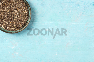 Chia seeds, close-up in a bowl, overhead shot on a blue background with copy space