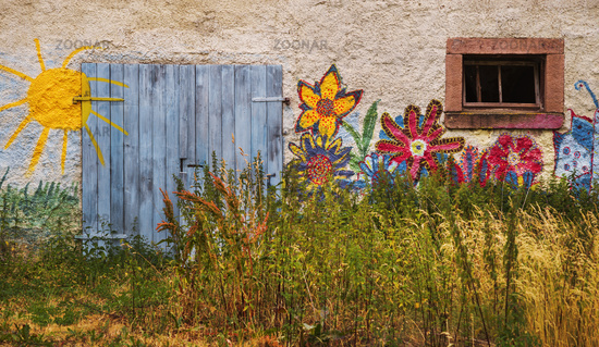 Children's paintings on a old house wall