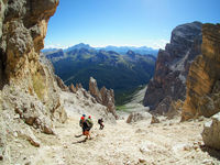 Group of mountain climber on a steep scree and rock descent in the Dolomites of Italy in Alta Badia