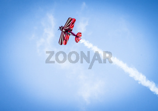Red plane with propeller flying upward