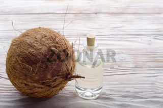 Coconut and oil in glass jar on white wooden table. Care concept