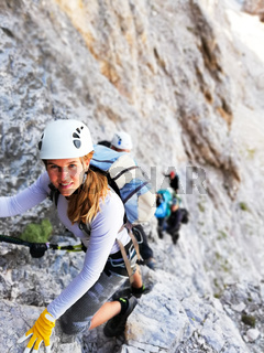 attractive blonde female mountain climber on a steep Via Ferrata in the Italian Dolomites