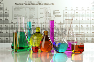 Test glass flasks and tubes with colored solutions on the periodic table of elements. Laboratory glassware. Science chemistry and research concept.