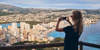 Young blond woman stands on fenced area climbed up on Penon de Ifach symbol of Calpe spanish touristic city, holds smartphone takes picture of scenery beautiful nature and cityscape above view. Spain