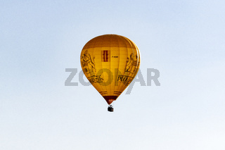 Hot Air ballon coming in the land with tourists.