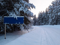 Winter road landscape with traffic sign
