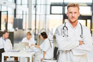 Junger Mann als Arzt mit verschränkten Armen