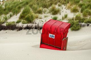 Roter Strandkorb vor den Dünen auf der Insel Helgoland, Schleswig-Holstein, Deutschland