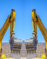 Reflection of an excavator facing away from the center of the symmetrical image during the day