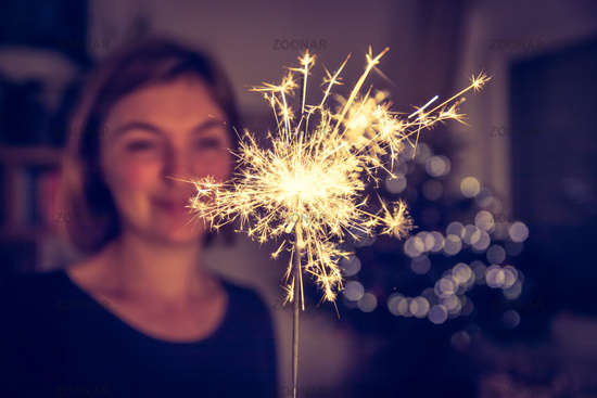 Happy girl is holding a sparkler at Christmas time