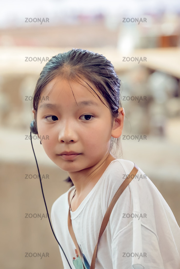 Little chinese girl with a listening device