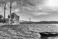 Ortakoy Mosque, the Bosphorus bridge and a boat by the pier, black and white image, Istanbul