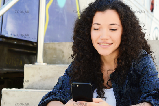 Young women sending message with smartphone.