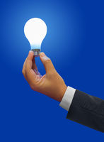 Lighting lamp in hand on blue