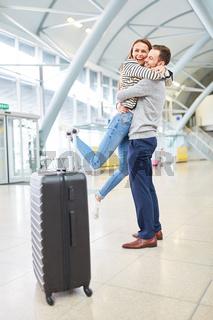 Junge Frau wird am Flughafen von ihrem Mann abgeholt