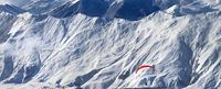 Paragliding at snowy mountains over ski resort and off-piste slope