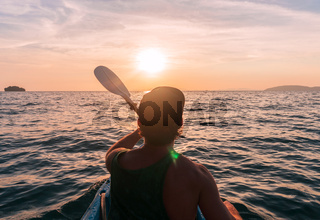 Kayaking. Man With kayak paddle at sunset sea Rowing to the Sun.