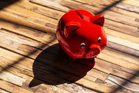 Red piggy bank casts a shadow