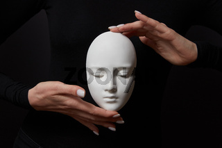 Two woman's hands hold white gypsum mask face on a black background. Concept social psychological masks