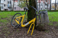 Yellow bicycle and dumpster of garbage