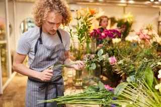 Florist oder Azubi beim Blumen binden im Laden