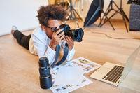 Fotograf vor dem Laptop mit Kamera und Print Fotos