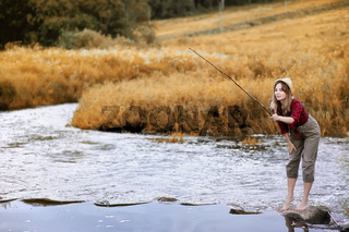 Girl in autumn with a fishing rod