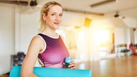 Frau mit Yoga Matte in Kursraum von Fitnesscenter