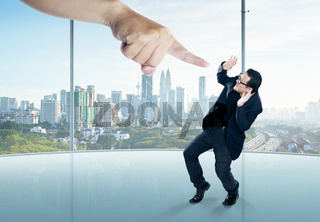 A scared businessman full-height in a scare pose and a giant hand pointing at him