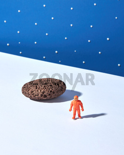 Plastic toy of spaceman and moonstone on a light surface against blue star sky background.