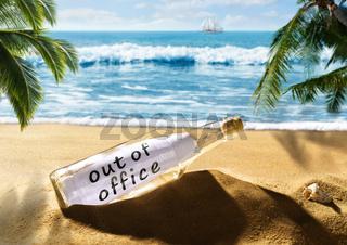 Flaschenpost mit der Nachricht out of office am Strand