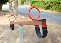 A close-up of empty brown wooden swing seat with red handles in the playground.