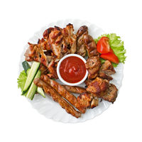 Grilled meat, sausages and tomato sauce on the plate, isolated on white background. Top view