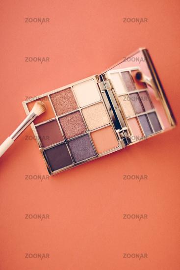 Eyeshadow palette and make-up brush on orange background, eye shadows cosmetics product as luxury beauty brand promotion and holiday fashion blog design