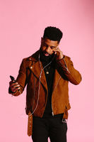 Stylish, handsome and cool African American man with beard, listening to music, texting, isolated on pink studio background