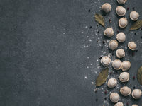 Beautiful scattered raw pelmeni on marble background
