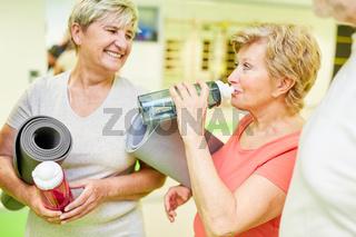 Seniorin trinkt aus einer Wasserflasche in einer Pause