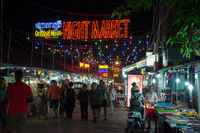 Busy night on the popular tourist Night Market street, with neon sign, Siem Reap, Cambodia.