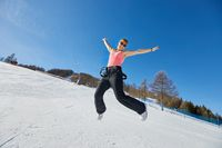 Woman jumping on a ski track in sunlight