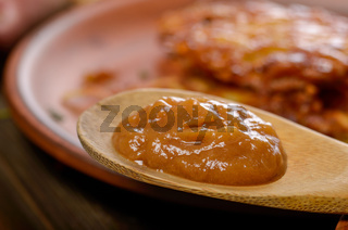 Applesauce in front of fresh homemade tasty potato pancakes in clay dish
