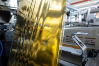 Industrial Label Printing Equipment Closeup Detail Gold Metallic Foil Embossing Web
