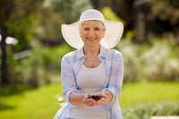 senior woman with handful of soil at summer garden