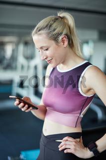 Sportliche junge Frau liest aufmerksam eine SMS