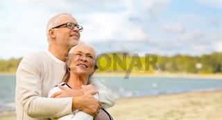 happy senior couple hugging over beach background