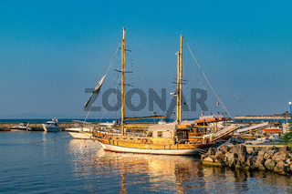 A classic wooden ship at sunrise docked in the harbor of Nessebar ancient city on the Bulgarian Black Sea Coast. A wooden ship with water reflection docked in the harbor at sunrise