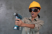 Portrait of attractive young girl builder with drill isolated over concrete wall