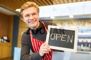 Junger Restaurant Gründer zeigt eine Kreidetafel