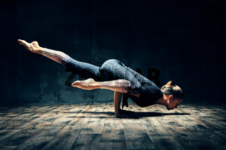 Young woman practicing yoga doing hurdler pose in dark room