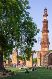 View on Qutb Minar Complex, with Minaret, antic ruins and vegetation. UNESCO World Heritage in Mehrauli, Delhi, India, Asia.