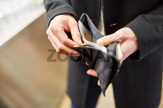Mann mit Portemonnaie beim Bezahlen mit Bargeld